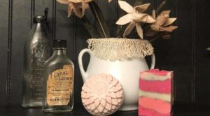 decorative fabric flowers in white pitcher, a bath bomb, a soap bar, and bottles